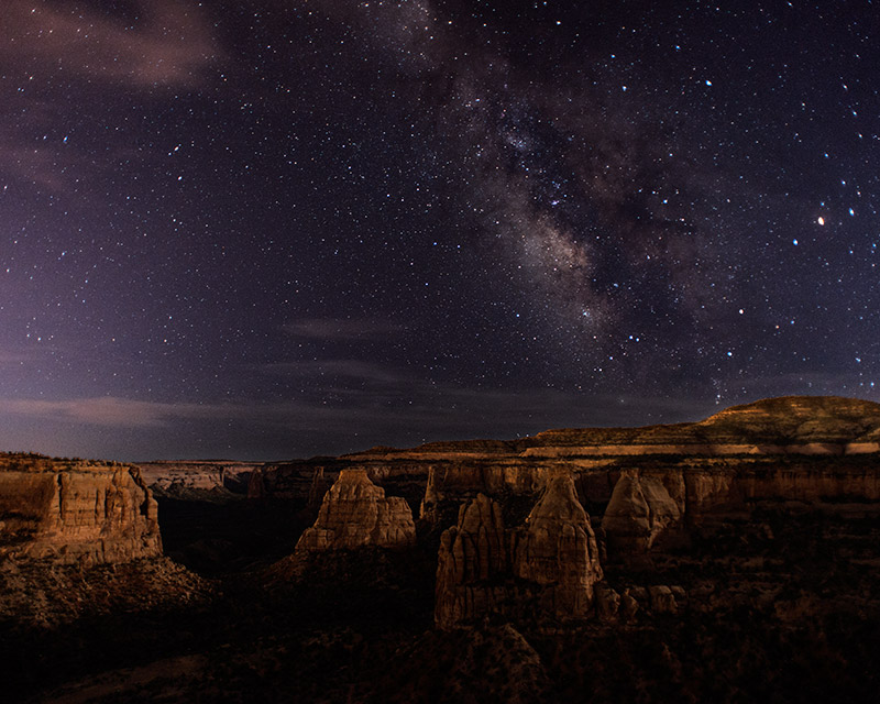 A first-quarter moon gives light and texture to the sandstone formations in Monument Canyon while the Milky Way shines overhead...