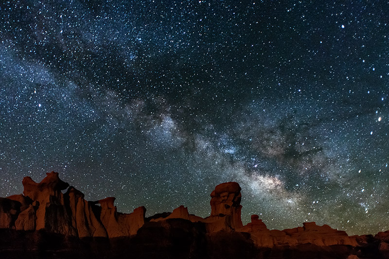 The center of the Milky Way galaxy rises early one spring morning over rock formations of the Bisti/De-Na-Zin Wilderness.