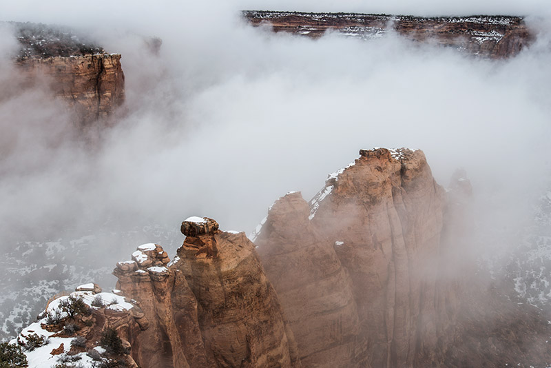 Clouds swirl up and around the red sandstone formations of the Colorado National Monument on an unusually warm February afternoon...