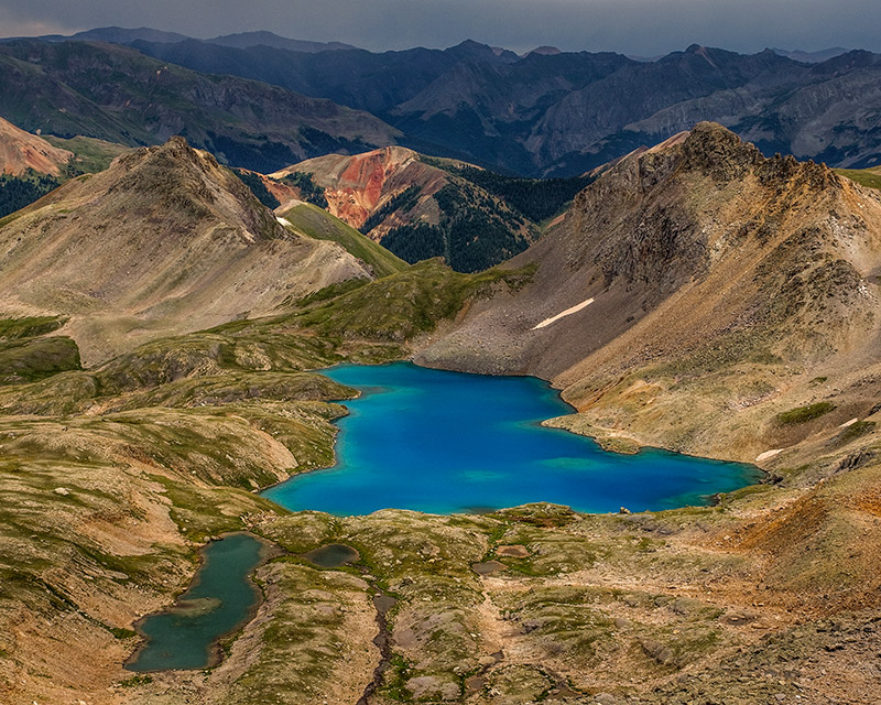 Columbine Lake, one of the many jewels of the San Juans, has a deep blue color produced by glacial silt that has washed down...