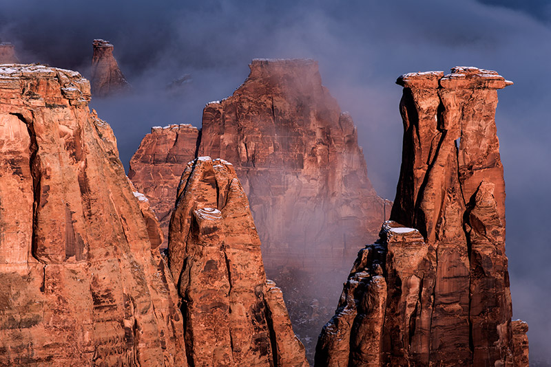 Fog creeps up the sandstone formations of the Colorado National Monument just after sunrise. After the very first light of the...