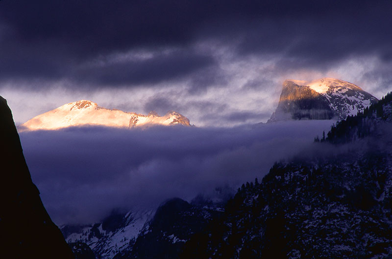 Half Dome peeks out from behind the clouds of a clearing winter storm in March 1999.