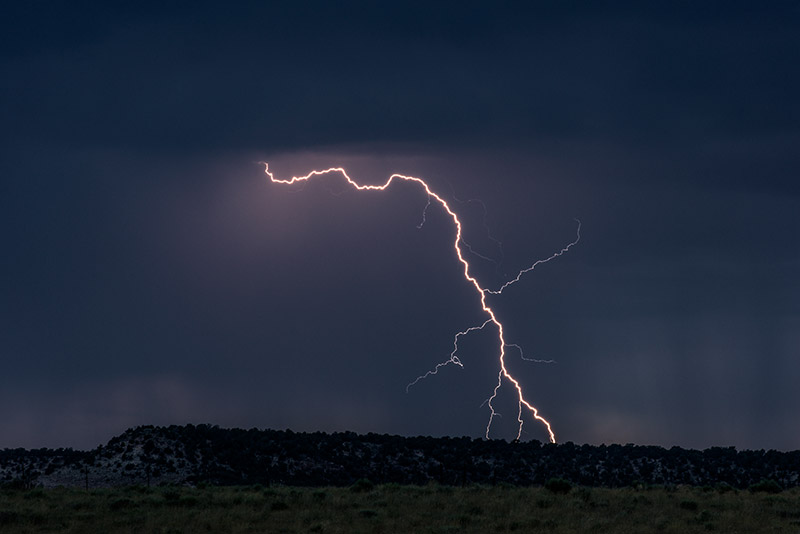 A single bolt of lightning branches into three simultaneous strikes on the ridge just north of my house in western Colorado. &...