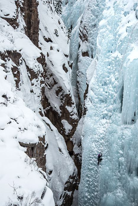 An ice climber emerges from the cold, dark depths of the Uncompahgre Gorge.