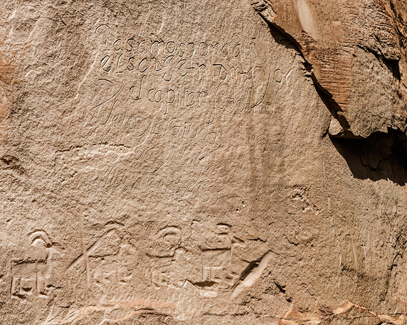 Ancestral Puebloans carved the images of the bighorn sheep at the bottom of this image. The Spanish inscription above reads...