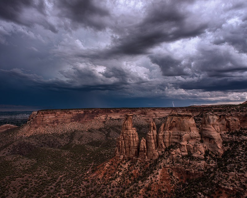 A single bolt of lightning further dramatizes a stormy scene in the Colorado National Monument.