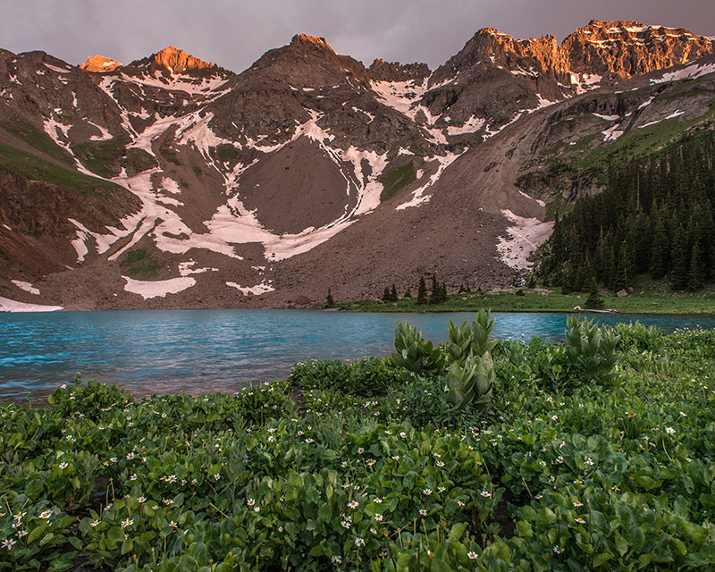 A stormy afternoon, typical for the San Juans in summer, breaks up just enough to allow a few rays of light to hit the upper...