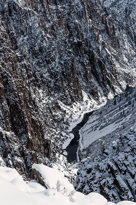 Muted sunlight passing through thin clouds rakes across the north wall of Black Canyon after new snow.