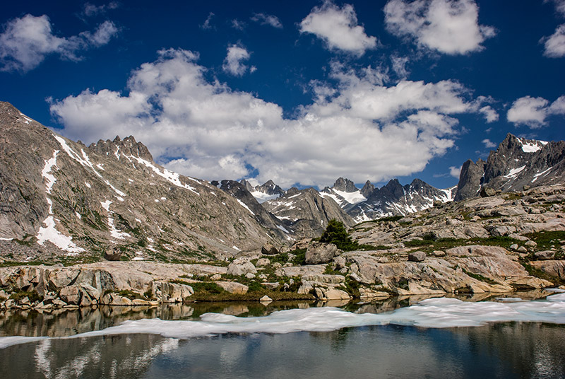 After a heavy snow year in 2008-2009, this tarn still had ice well into August. Wyoming's highest peak, Gannett, sits just...